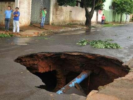 Asfalto cede, enxurrada abre cratera no meio de rua e família fica ilhada