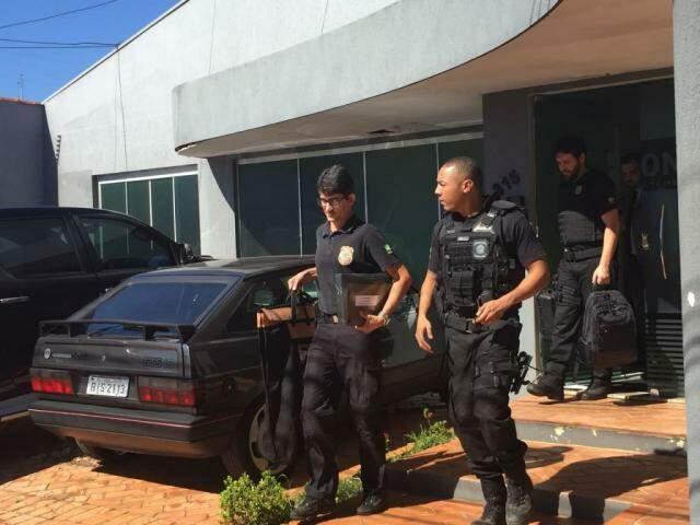 Policiais saindo com malote do Instituto Ícone. (Foto: Bruna Kaspary)