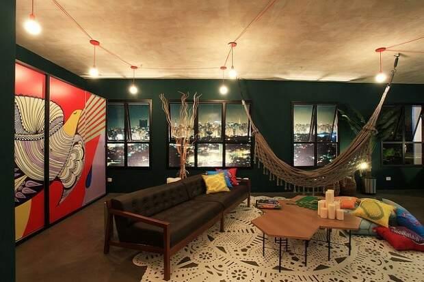 Parede com cor forte, quadros e decorações coloridas e a rede continua sendo peça chave
