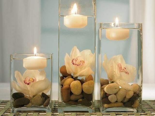 Nos vasos, um pouco de água, pedras, flor e vela.