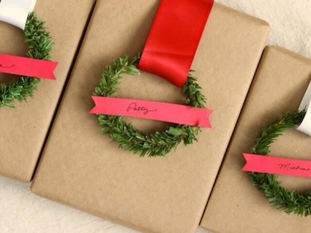 Embalagem de papel pardo, com fita e um pedaço de galho de árvore de Natal em formato de circulo. Para fechar, um pedaço de papel Color7, para o nome do destinatário.