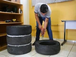 Aluno fura pneu para encaixá-lo nos demais com ajuda de parafusos. Goma branca entre os pneus é silicone usado para evitar que água vaze antes de ser tratada (Foto: Paulo Francis)