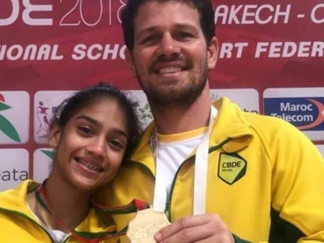 Leticia Menino com o técnico Igor Rocha e a medalha de ouro dos Jogos Mundiais Escolares (Foto: Arquivo pessoal)