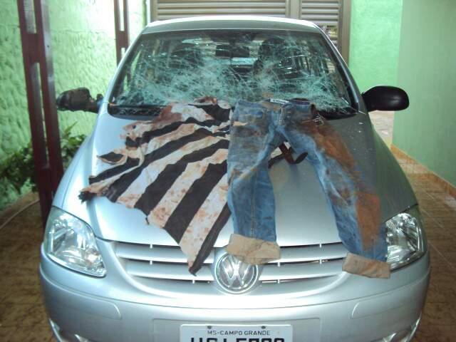 Carro de Samuel com roupas sobre o capô, que foi quebrado durante a briga.