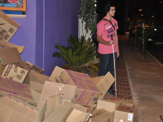 Em meio a caixas, Rafael precisa parar de seguir trajeto pela pista tátil. Exemplo de barreira móvel. (Foto: Simão Nogueira)