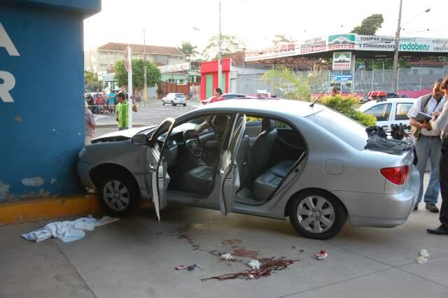 Corolla com o casal foi parar na parede do posto da PM na antiga rodoviária. Manchas de sangue ficaram no carro e no chão. (Foto: Wendell Reis)