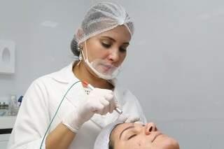 Jozi utiliza aparelho de alta frequência para cauterização da pele. (Foto: Marcos Ermínio)
