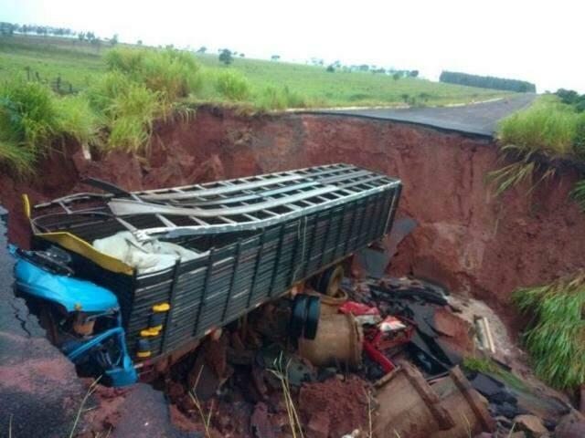 Caminhão boiadeiro caído em buraco aberto pela chuva na MS-475 (Foto: Nova News)