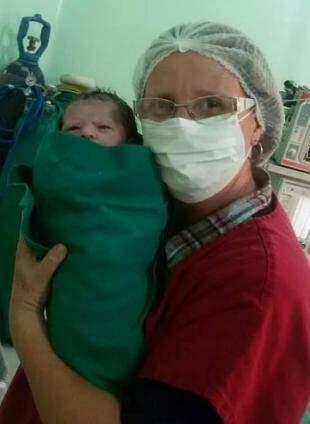 Com um dos bebês que assistiu nascer. (Foto: Arquivo Pessoal)