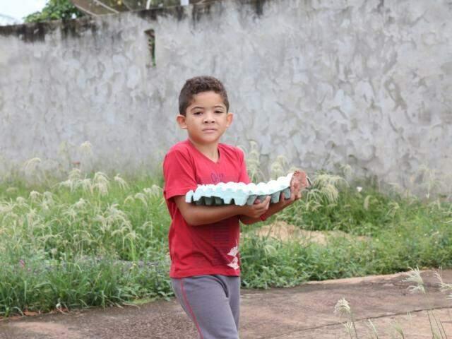 Menino volta de mercado de Terenos com cartela cheia de ovos; consumo per capita no país é de 190 ovos por ano (Foto: Marcos Ermínio)