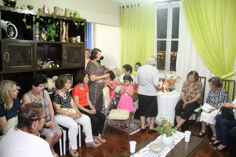 Na sala de casa, Irene reúne amigos, vizinhos e familiares num terço de gratidão.