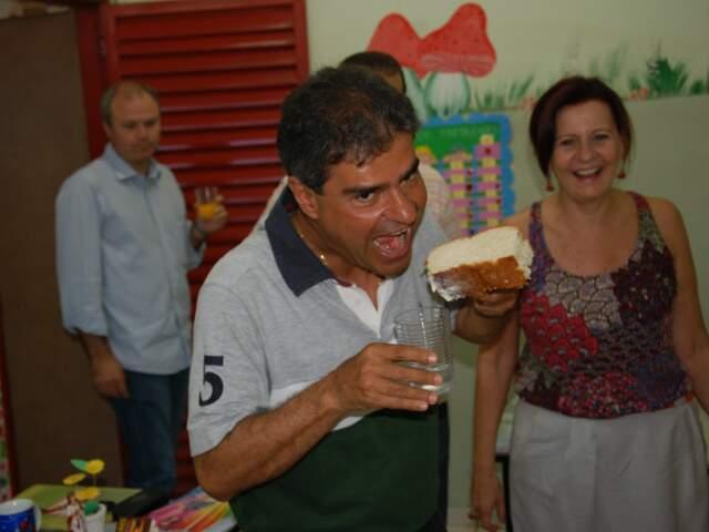 Prefeito brinca com pão servido durante café da manhã em escola onde entregou kits de material aos estudantes.