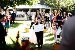 """Antes que a noiva entrasse, priminho anunciou com a placa """"lá vem... """" (Foto: Renan Kubota)"""