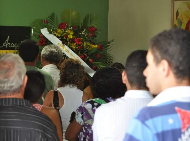 Parentes e amigos no velório de vítimas de acidente. Ao fundo, coroa enviada pelo Marfrig (Foto: Marlon Ganassin)