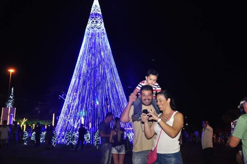 Camila e a família olhavam as fotos tiradas com a árvore de Natal de fundo, nas cores azul e branca.