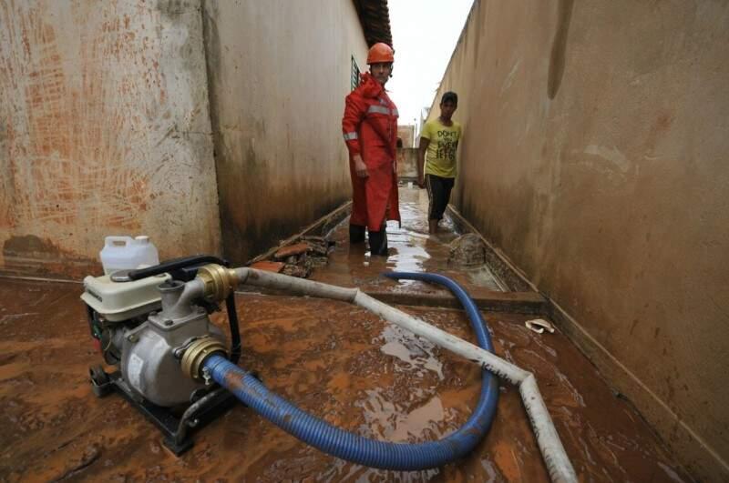 Bombeiros retiram água com auxílio de bomba. (Foto: Alcides Neto)