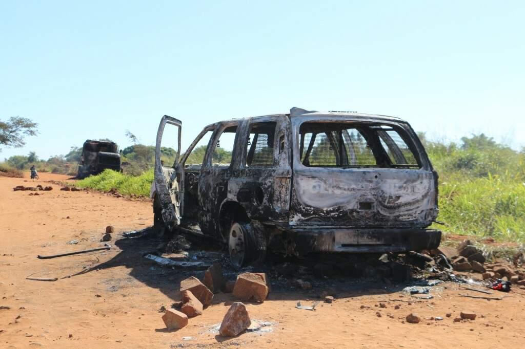 Viatura da PM queimada por índios; ao fundo, caminhão e colheitadeira também incendiados (Foto: Helio de Freitas/Arquivo)
