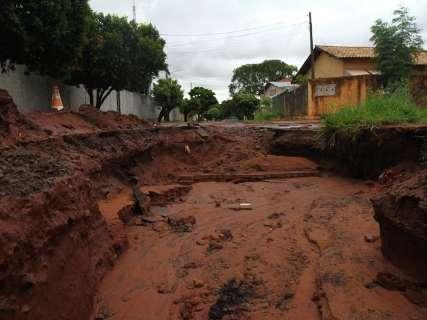 Chuva rápida abre cratera de 6 metros em obra inacabada e interdita rua
