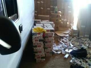 Caixas de cigarros no chão, ao lado da van que transportaria mercadoria. (Foto: Divulgação PMMS).