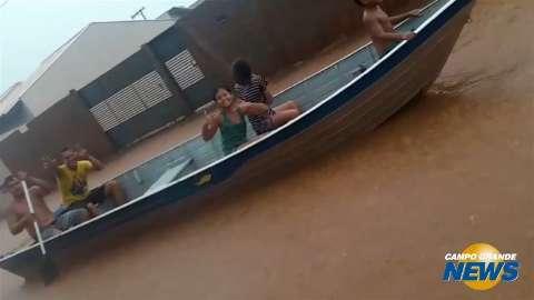 Com bom humor, moradores andam de barco em rua alagada