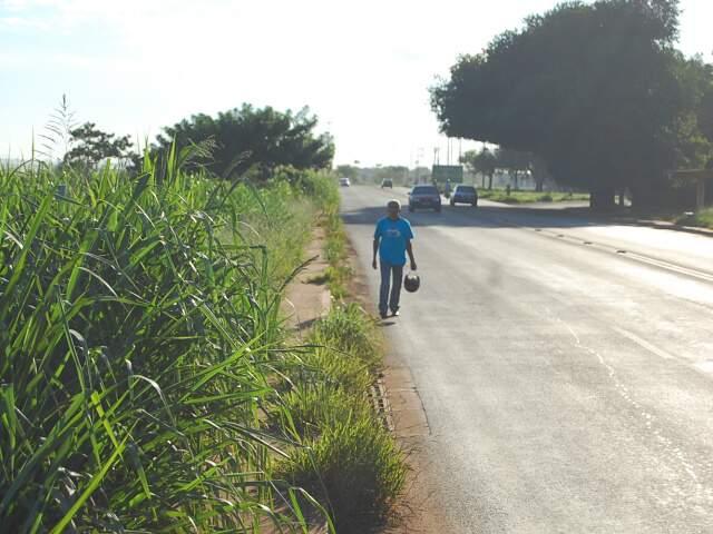 Algumas placas de sinalização estão encobertas e os pedestres dividem a calçada com o mato alto às margens da BR. (Foto: Marlon Ganassin)