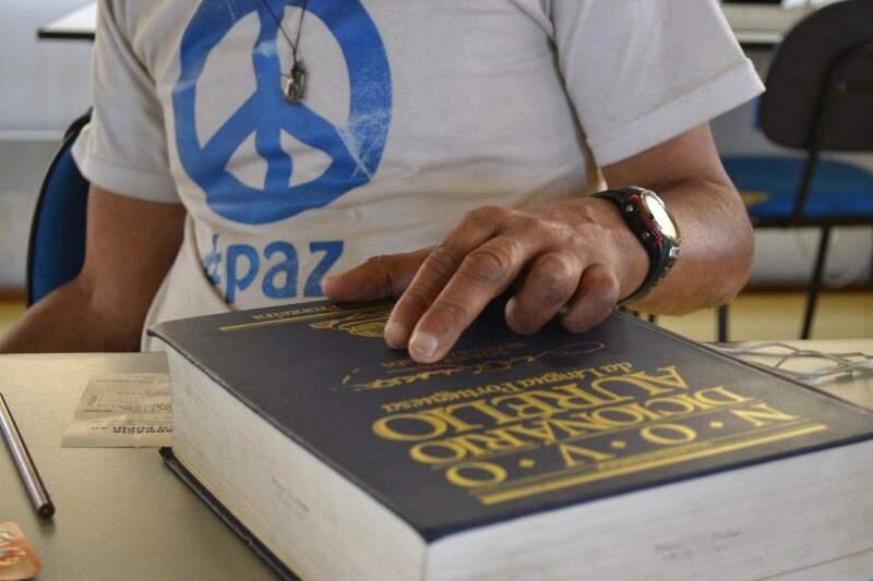 Dicionário é acessório enquanto desabrigado busca conhecimento nos livros espíritas. (Foto: Thailla Torres)