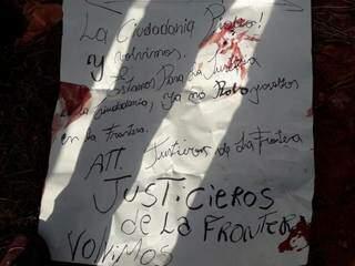 """Cartaz deixado por """"Justiceiros da Fronteira"""" ao lado de corpo (Foto: Direto das Ruas)"""
