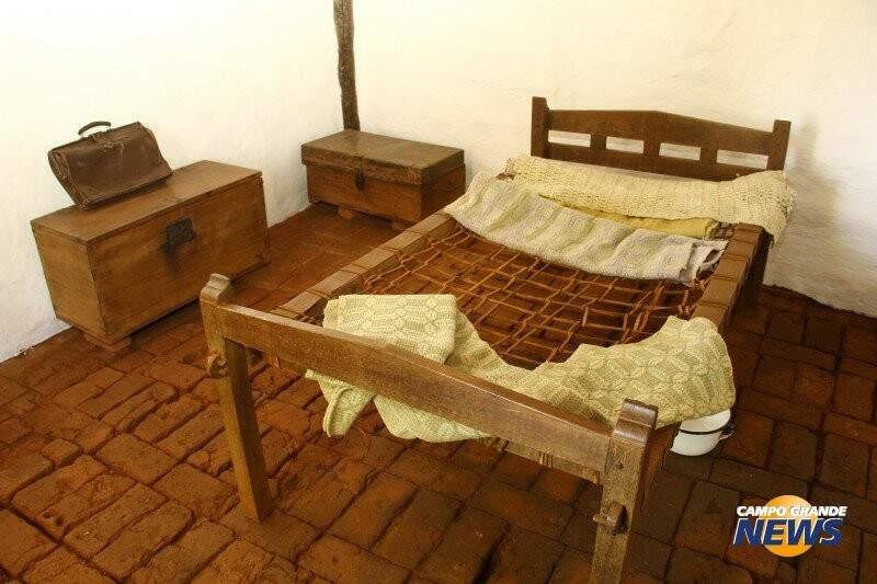 Cama sobre piso de tijolos, baús, lençóis, peças originais no museu em homenagem ao fundador de Campo Grande (Foto: Arquivo)