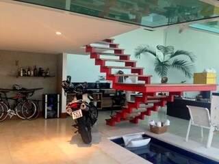Em vermelho Ferrari, escada funciona como escultura e flutua acima da piscina. (Foto: Daniel Moura/DL Arquitetura e Construção)