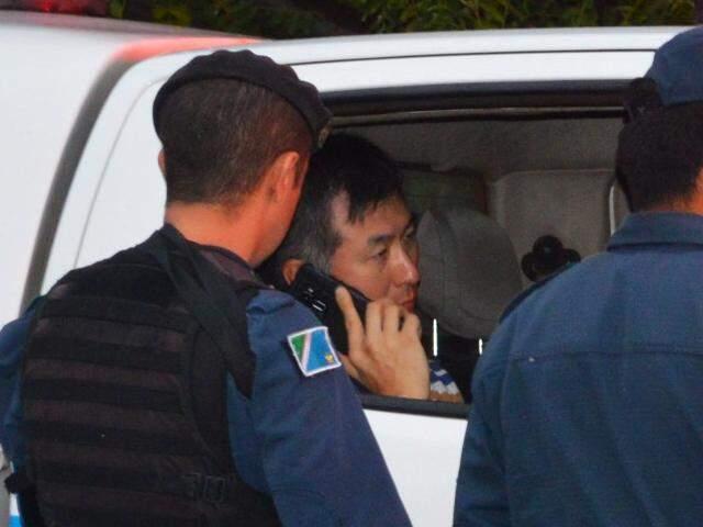 Dentro da viatura da PM, coreano fala ao celular (Foto: Simão Nogueira)