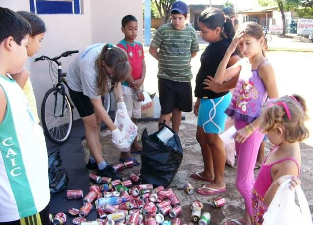 Crianças recolhem materiais que podem acumular água. (Foto: Divulgação)