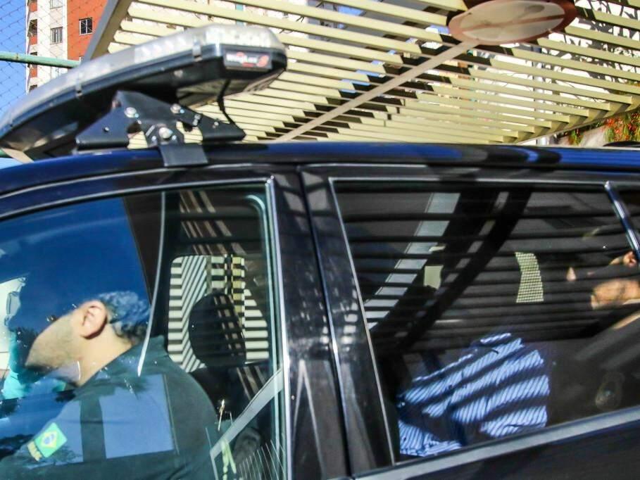 No banco de trás da viatura, Puccinelli deixa casa dele em direção à Polícia Federal (Foto: André Bittar)