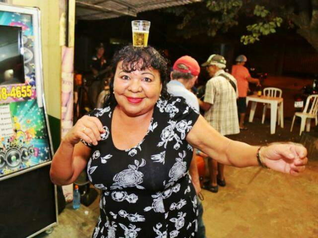 Raimunda é uma das mais animadas no bar. Dança, canta e de mesa em mesa distribui sorriso durante a noite. (Foto: Fernando Antunes)