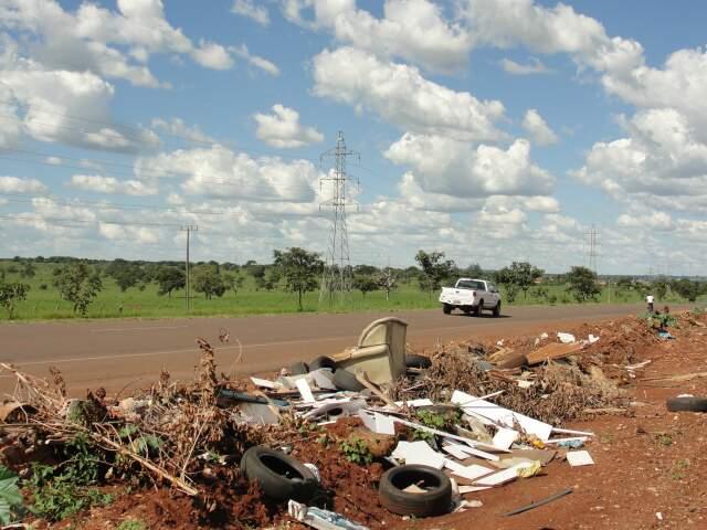 Ao longo da rodovia é possível ver amontoados de lixo, como restos de árvores, materiais de construção, pneus velhos e até sofá velho. (Foto: Lucimar Couto)