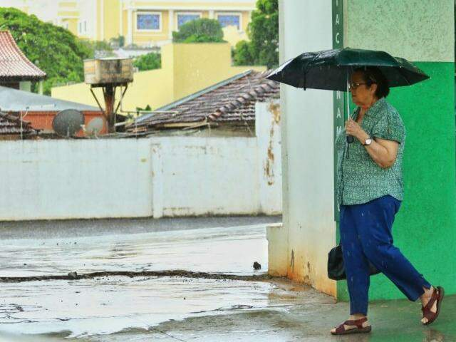 Senhora se protege de chuva no centro de Campo Grande (Foto: André Bittar)