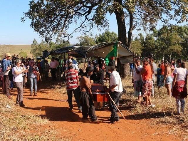 Índios carregam caixão com o corpo de Clodioudo após sobrevoo de helicóptero em fazenda (Foto: Helio de Freitas)