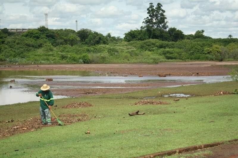 Feito de forma manual, trabalho de limpeza não é suficiente para conter assoreamento do Lago do Amor (Foto: Marcos Ermínio)