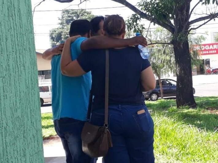 Pai (de camisa azul) saindo da delegacia, onde foi registrar o caso, amparado por amigos (Foto: Geisy Garnes)