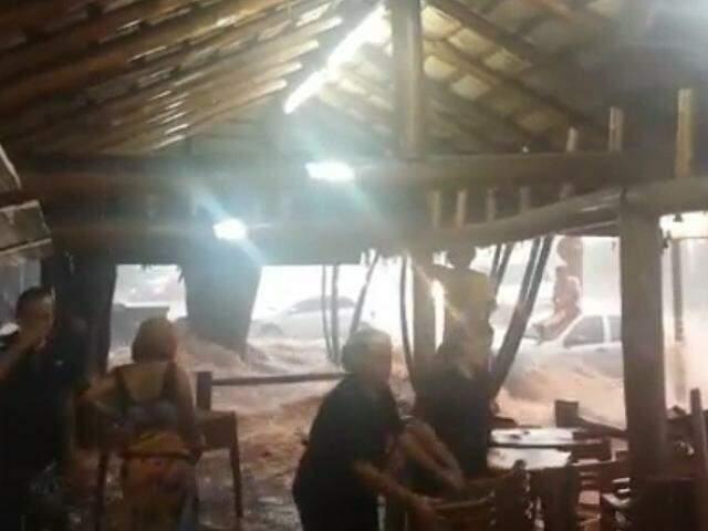 Funcionários da lanchonete correm para retirar mesas e cadeiras em meio à enxurrada (Foto: Reprodução/Direto das Ruas)