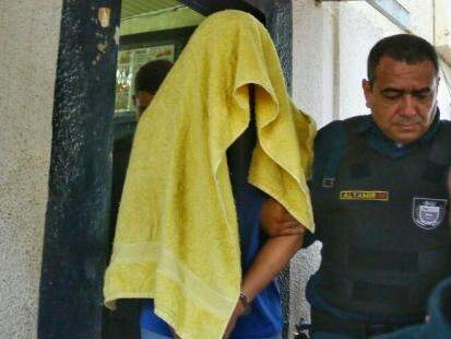 Algemado e com toalha na cabeça cobrindo o rosto, Ricardo Moon deixou o Centro de Triagem na manhã de hoje. (Foto: André Bittar)