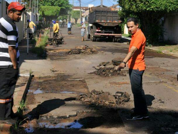 Equipes trabalham em rua tomada por buracos este sábado. (Foto: Alcides Neto)