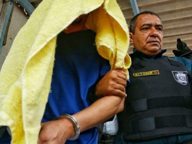 Algemado e com toalha na cabeça cobrindo o rosto, Ricardo Moon é levado para Agepen, onde deve colocar a tornozeleira e ser liberado (Foto: André Bittar)