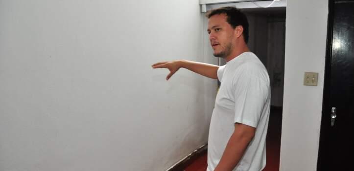 Vitor mostra parede branca que será grafitada.