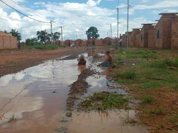 No Pedro Teruel, crianças brincam em poça d'água em frente à casa inacabada. (Foto: Simão Nogueira)