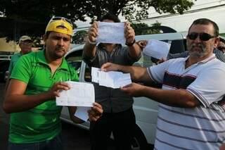 Motoristas mostram hollerites sem horas extras. (Foto:Fernando Antunes)