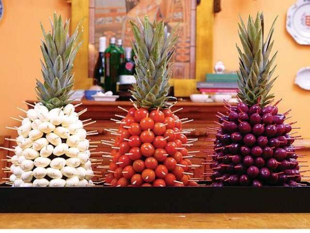 Três abacaxis e uma mesa tropical.