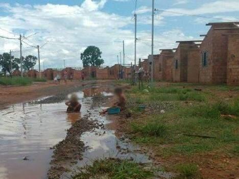 No Pedro Teruel, crianças moravam na Cidade de Deus brincam em poça d'água em frente a casas inacabadas (Foto: Simão Nogueira)