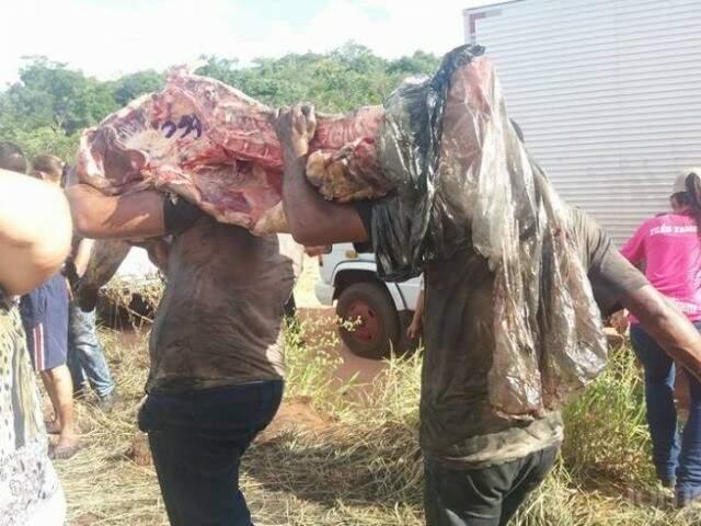 População saqueia carne após incêndio em caminhão (Foto: Nova Alvorada Notícias)