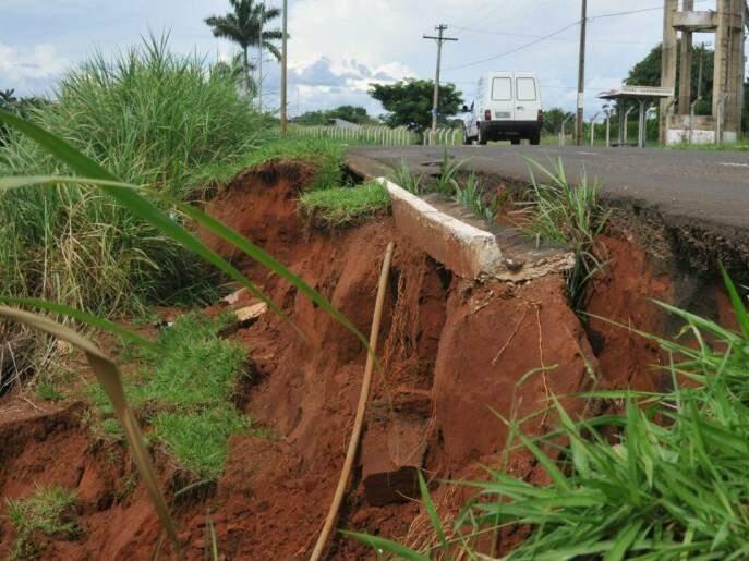 Em vários trechos, margens do rio Anhanduí estão desmoronando e parte da pista está comprometida (Foto: Alcides Neto)