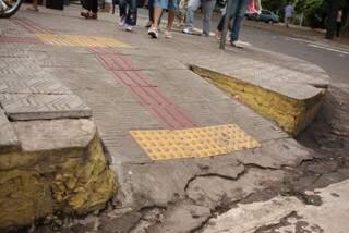 Av. Afonso Pena equina com Rua 14 de Julho - Presença de desnível entre o final do rebaixamento e o asfalto, além de a superfície do piso apresentar buracos e rachaduras, dificultando a travessia de pedestres e oferecendo risco à segurança. (Foto: Giuliano Lopes)